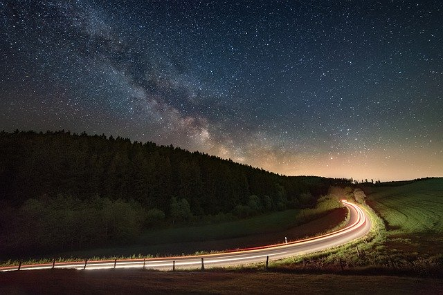 A road lit up under a starry night sky