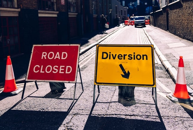 A road closed sign and a diversion sign