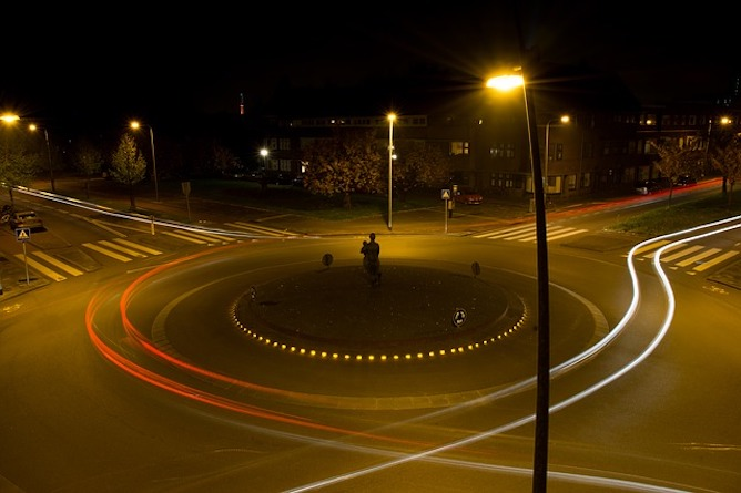 A roundabout with long exposure of headlights going around it