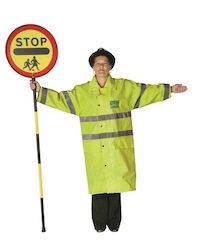 A school crossing patrol holding her sign vertically and holding her other arm straight out to the side