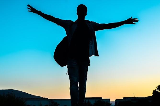 The silhouette of a man with his arms outstretched against a bright blue sky
