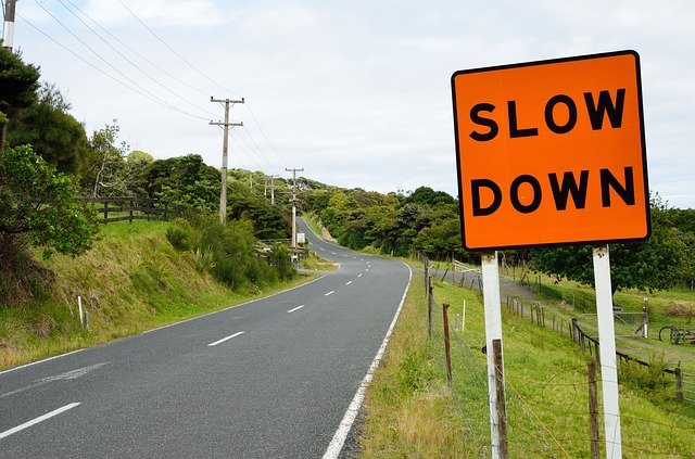 A road sign saying slow down