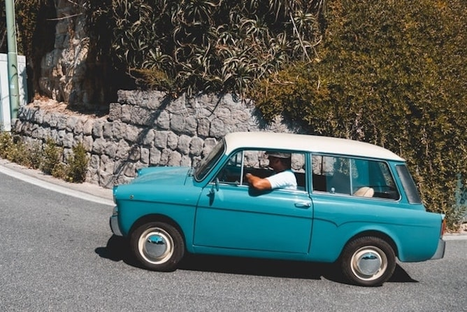 A small blue car without hill start assist being driven up a steep hill