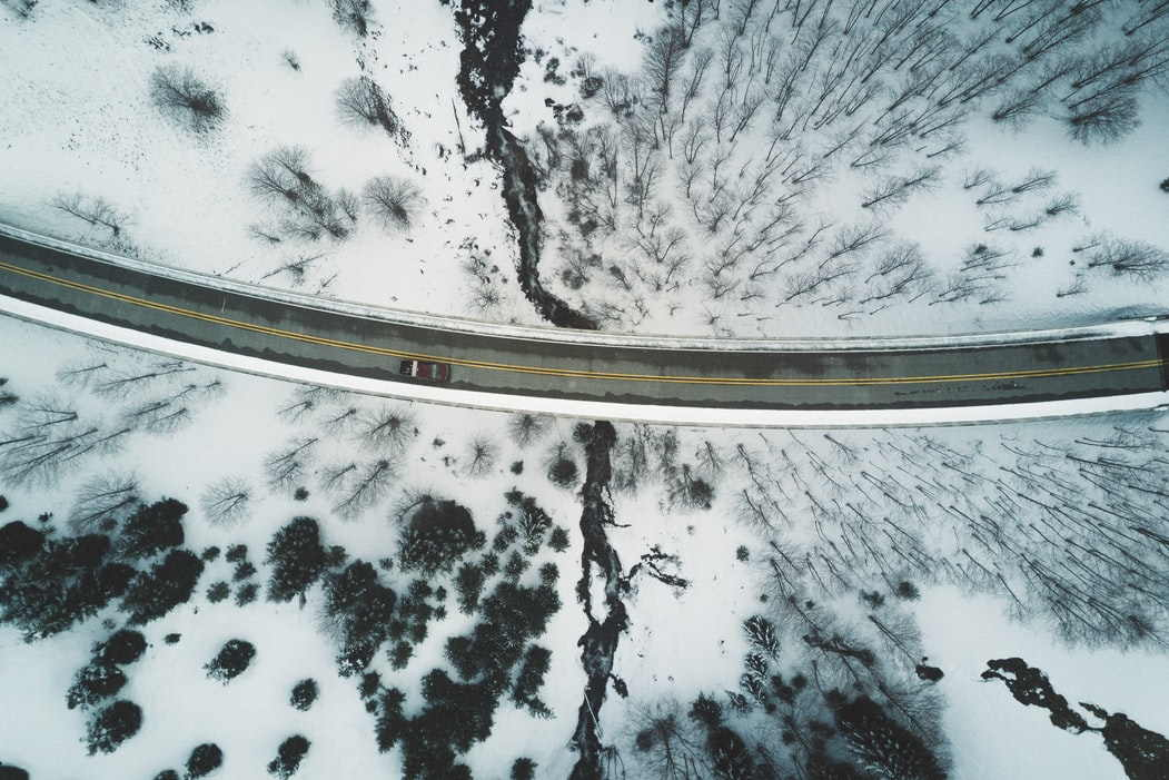 Birds eye view of road surrounded by snowy land