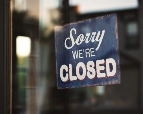 Blue 'sorry we're closed' sign hanging on door