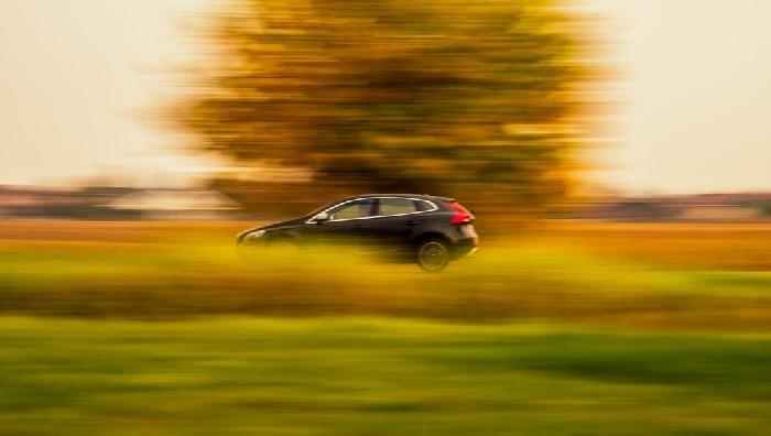 Black car speeding past tree