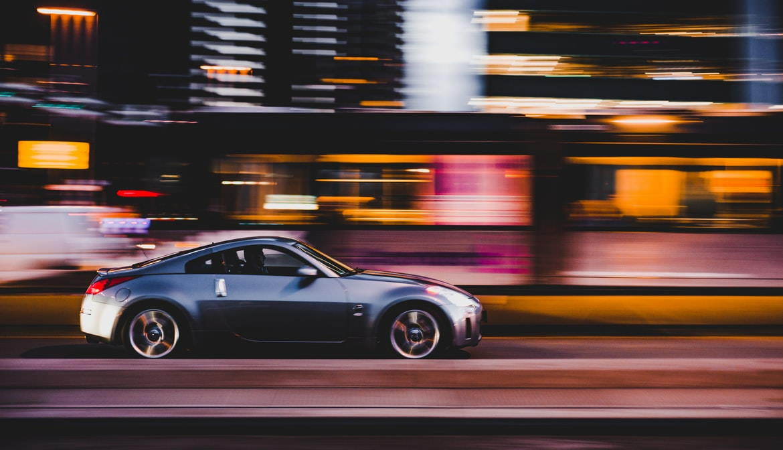 Grey sports car speeding past buildings