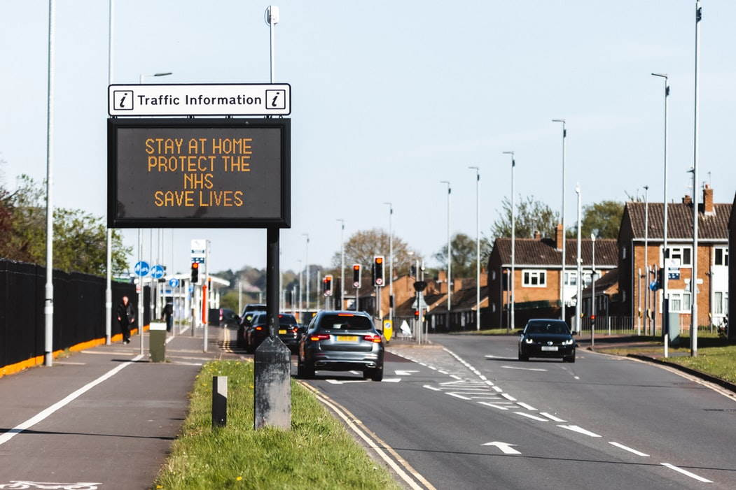 Road sign reading 'stay at home protect the NHS save lives'