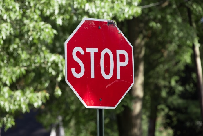 Stop road sign in front of foliage