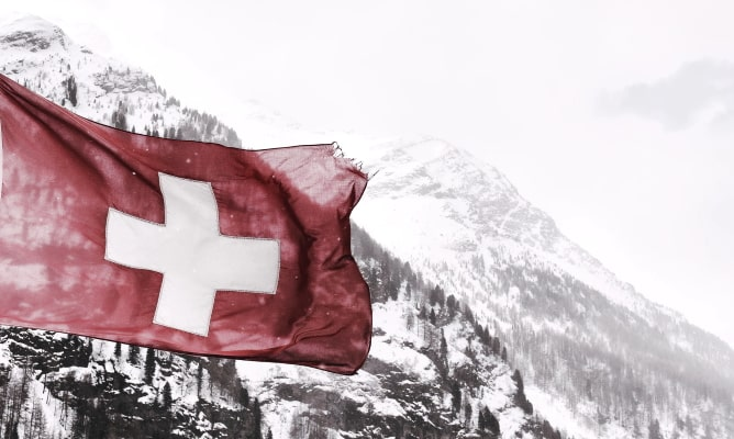 Swiss flag flying next to snow-covered mountains
