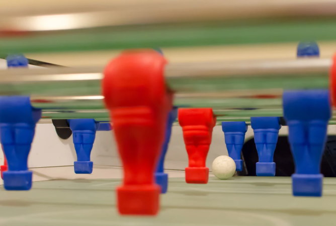 Close up of table football featuring red and blue figures and ball