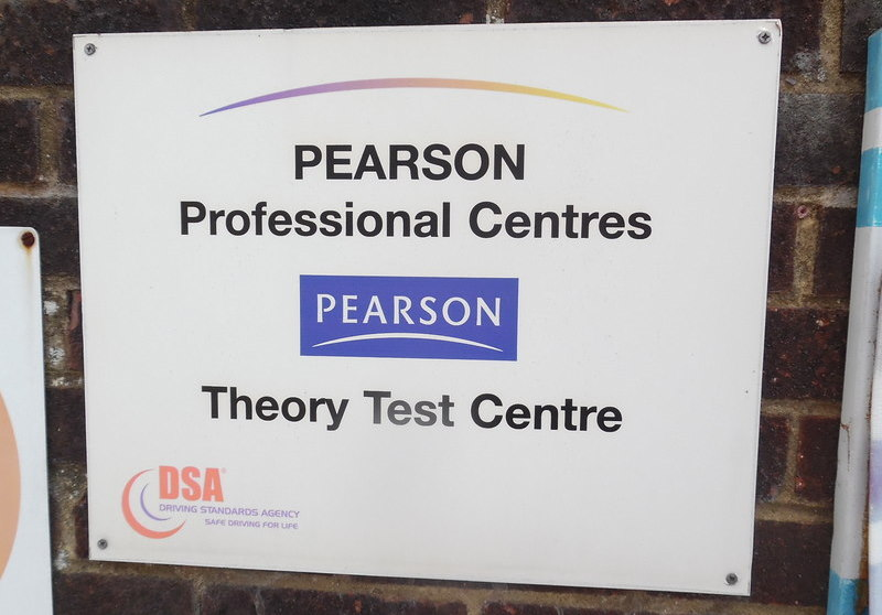 Sign outside a driving theory test centre. Sign reads PEARSON Professional Centres. Theory Test Centre'