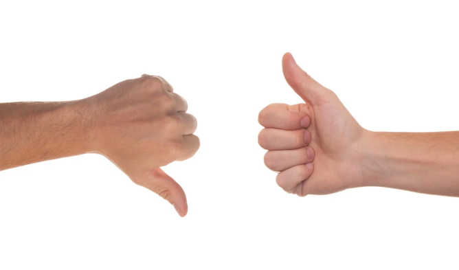 """Two hands, one performing a """"thumbs up"""" gesture and one """"thumbs down"""""""