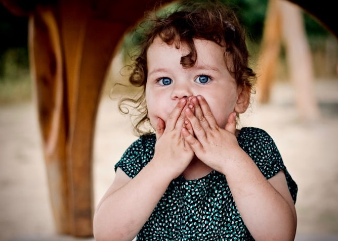 A toddler covering her mouth with her hands