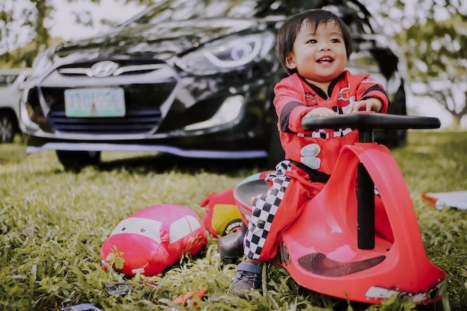 A toddler driving a toy car