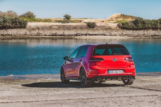 A red Volkswagen Golf next to a blue lake