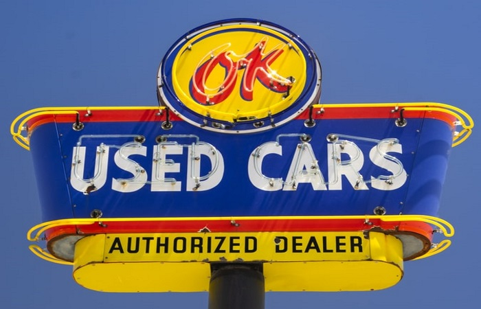 A blue and yellow used car sign