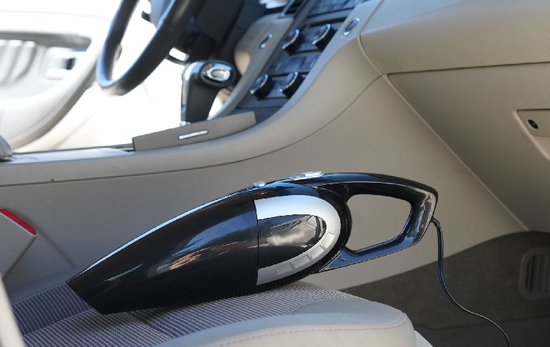 Handheld vacuum cleaner on front seat of car