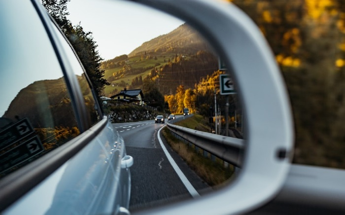 View of other cars on country road from a wing mirror