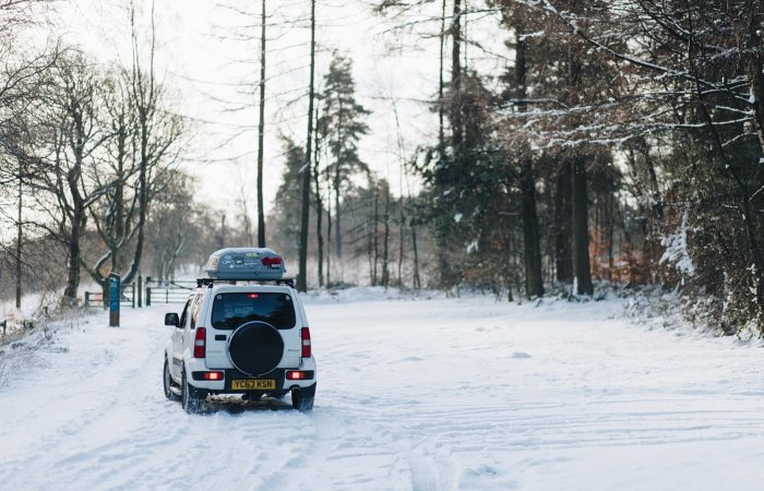 White car with a roof box driving in the snow next to forest