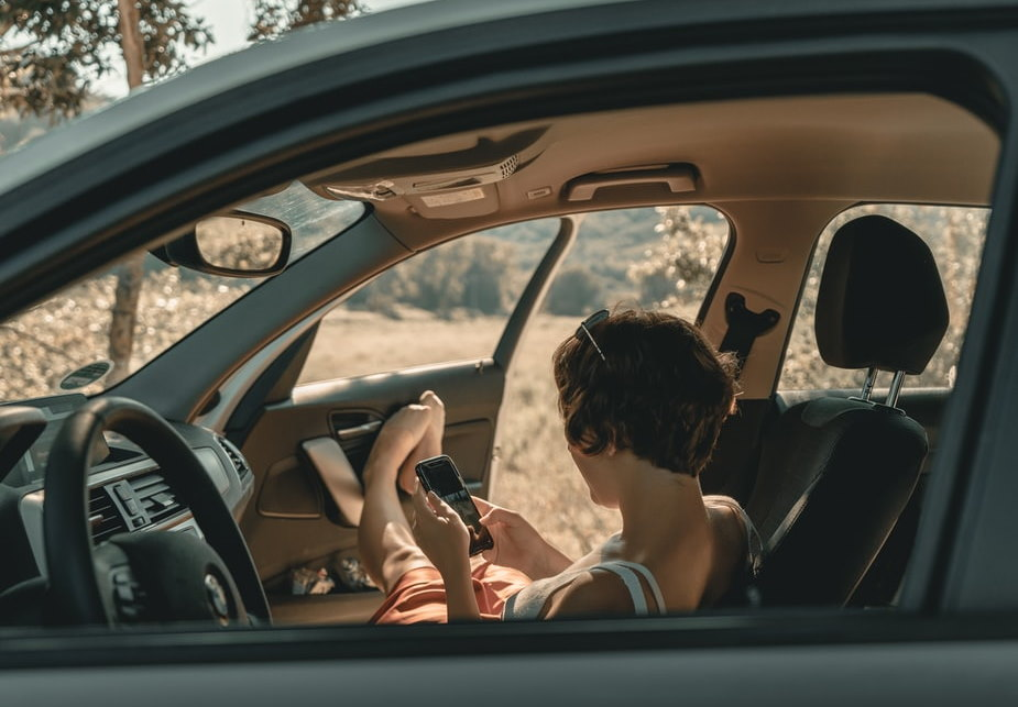 Woman sat in car looking at phone with feet resting on open car doorup looking