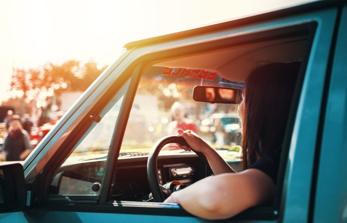 Woman holding steering wheel whilst staring out of windscreen in summer