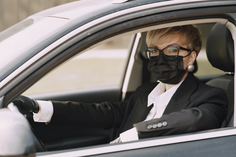 Woman in suit wearing a face mask while driving