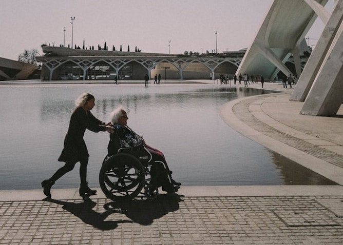 A woman pushing someone in a wheelchair beside water
