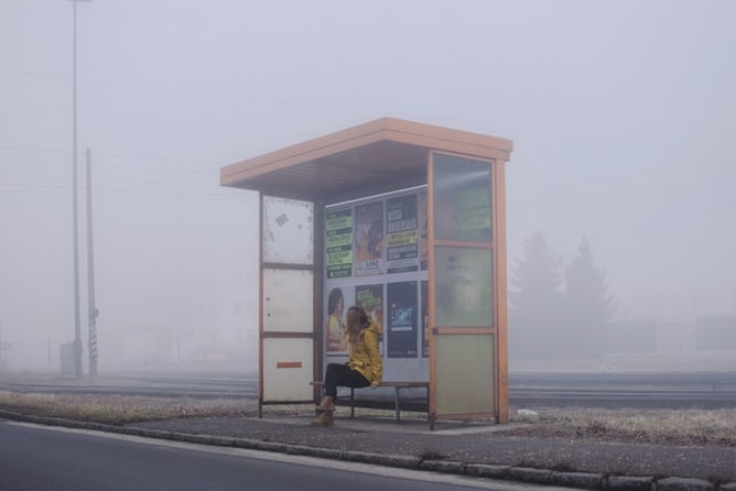 A woman waiting at a bus stop on a misty day