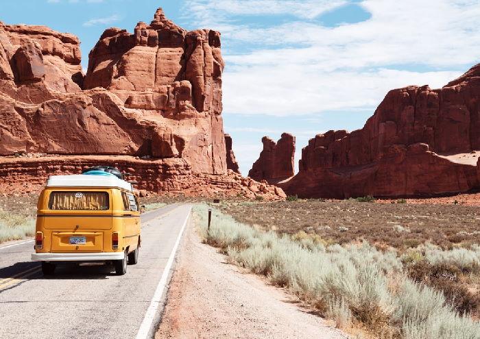 Yellow camper van driving along desert road