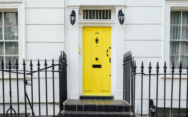 Yellow front door on white house with metal fence