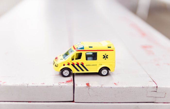Yellow toy ambulance on white bench