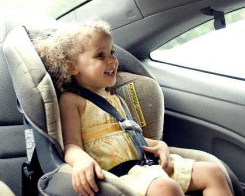 Young girl in a carseat smiling